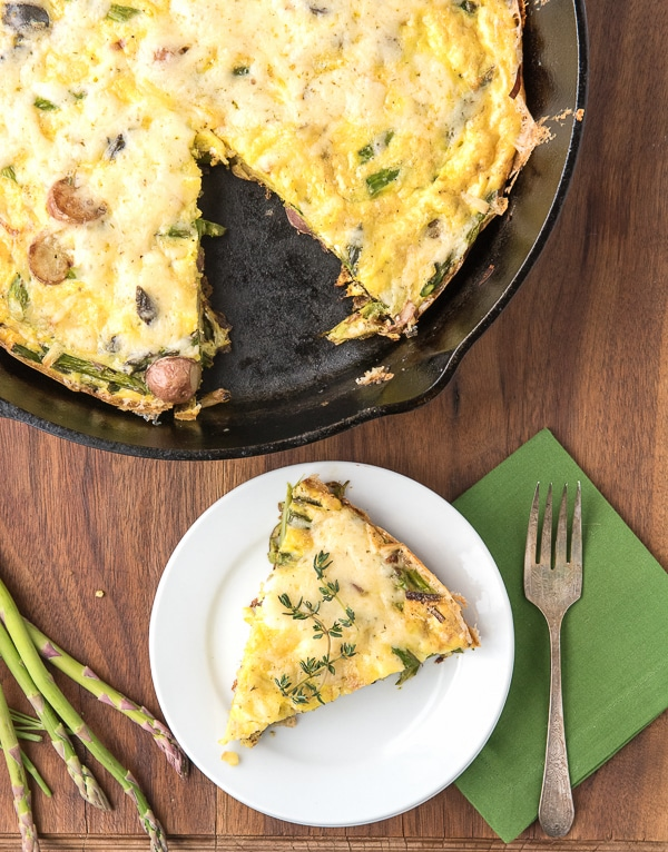 Cooked potato frittata in a cast iron pan with a slice on a white plate placed on a brown wooden table
