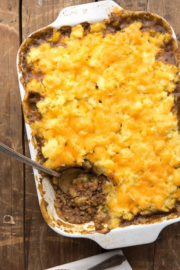 Savory Traditional Cottage Pie in white baking dish with scoop removed showing ground meat with vintage serving spoon