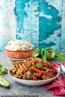 Batch of Spicy Southwestern Steak Stir Fry in a white bowl with Cilantro-Lime Rice and lime juicer
