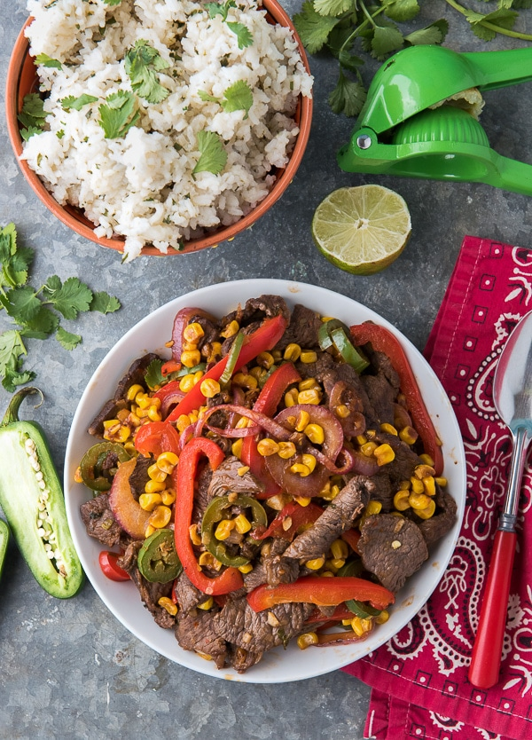Bowl of Spicy Southwestern Steak Stir Fry with Cilantro-Lime Rice and lime slices