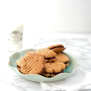 Peanut Butter and Jelly Sandwich Cookies (grain-free, gluten-free, ready in 30 minutes) on a ruffled blue plate with a glass of milk - BoulderLocavore.com