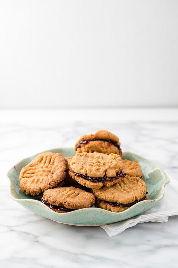 Peanut Butter and Jelly Sandwich Cookies that are gluten-free and easy to make on a blue plate - BoulderLocavore.com
