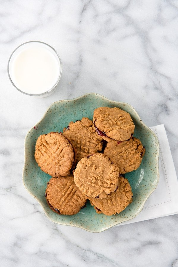 Peanut Butter and Jelly Sandwich Cookies on a blue plate with milk. Grain-free, gluten-free, ready in 30 minutes! - BoulderLocavore.com