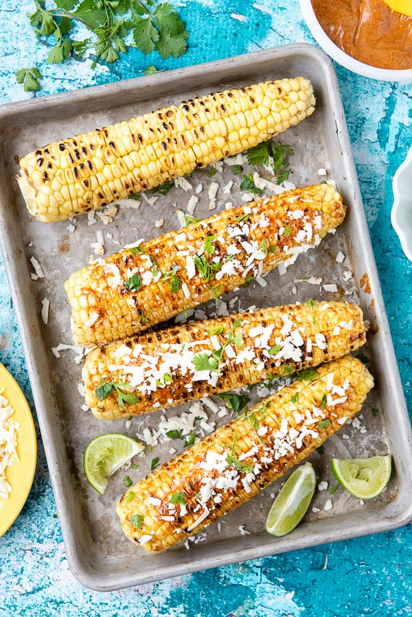 Grilled Mexican Corn Elote on a metal baking sheet with lime wedges