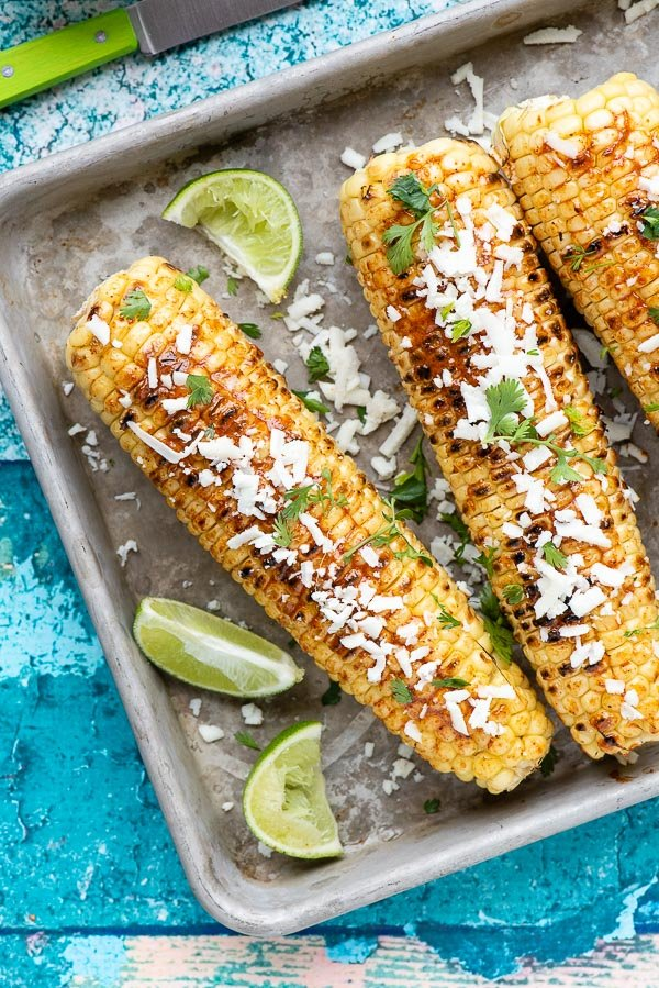 Grilled Mexican Corn Elote with crumbled cotija cheese and limes