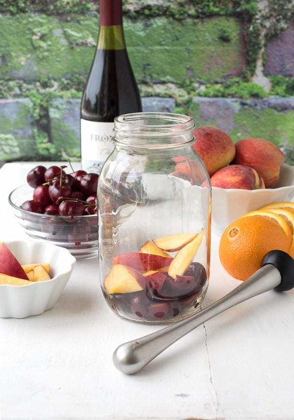 Summer Solstice wine cocktail - muddling cherries and peaches - BoulderLocavore.com