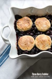 Three Berry Cobbler with Sour Cream Biscuits in a white ruffle-edged baking dish