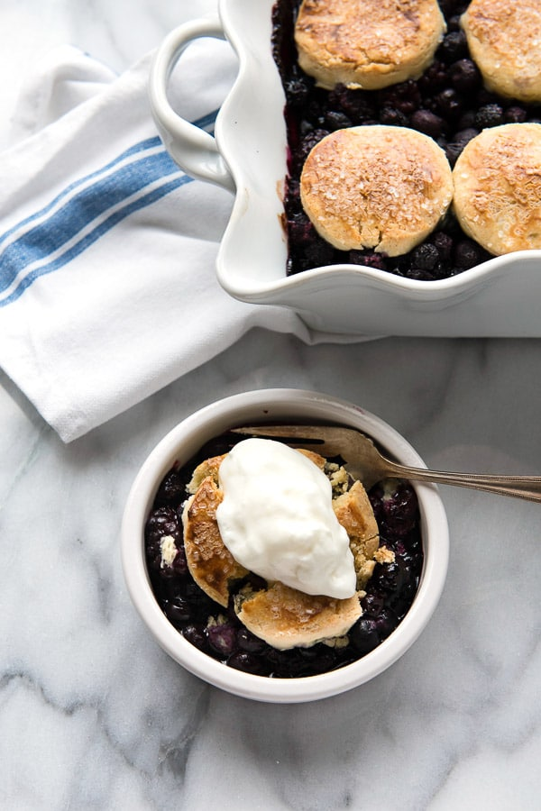 A single serving of Three Berry Cobbler with Sour Cream Biscuits with a dollop of freshly whipped cream