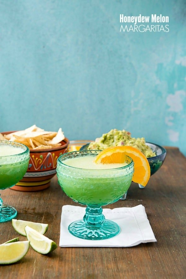 Two blue glasses of Honeydew Melon Margaritas (an easy margarita recipe) with salted rims and orange slices