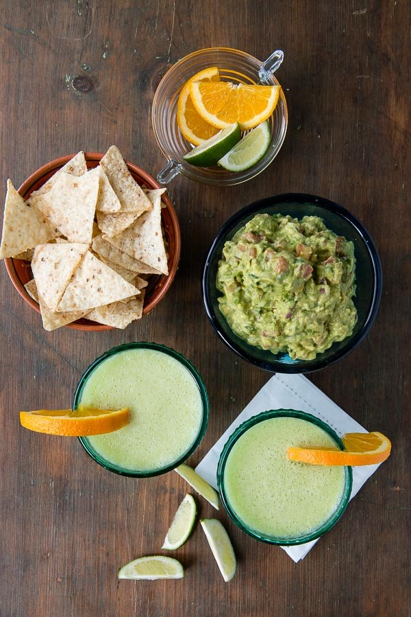 Honeydew Melon Margaritas with orange slices, lime wedges, bowl of chips, freshly made guacamole on a vintage wooden surface