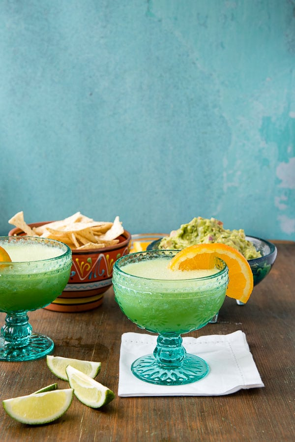 Two Honeydew Melon Margaritas with orange slices on the glass rim, lime wedges, chips in the background