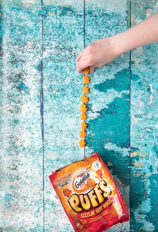 Child\'s Hand picking up gluten-free Goldfish Puffs