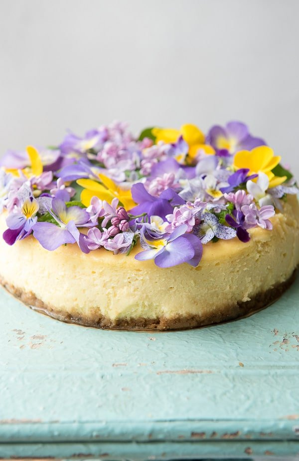 Lemon Cheesecake with Vanilla Wafer Crust and Edible Flowers  on green tray