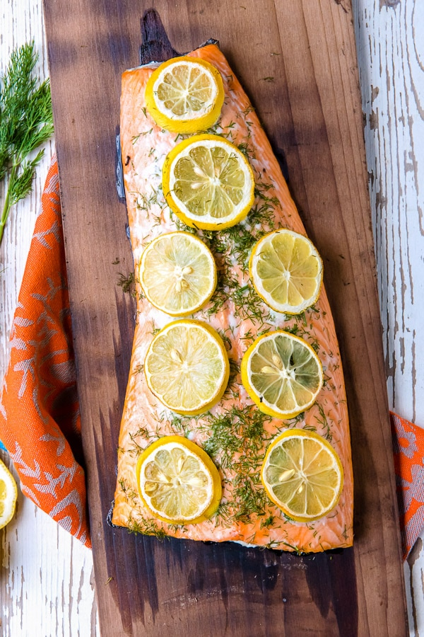 Charred cedar plank salmon cooked with dill and lemon slices