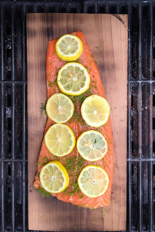 Salmon grilling on a charred cedar plank with lemon slices