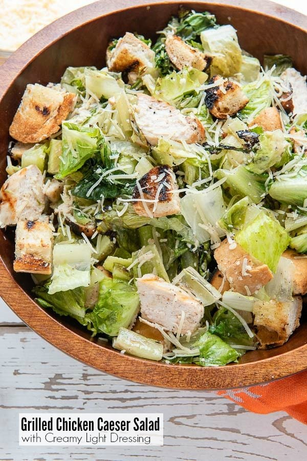 Wooden bowl of Grilled Chicken Caesar Salad with light creamy dressing