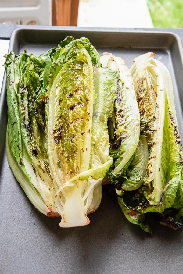 Grilled heads of romaine lettuce on a sheet pan