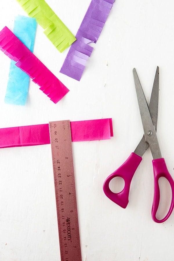 How to Make a Rainbow Milk Carton Pinata tutorial cutting tissue paper strips- BoulderLocavore.com