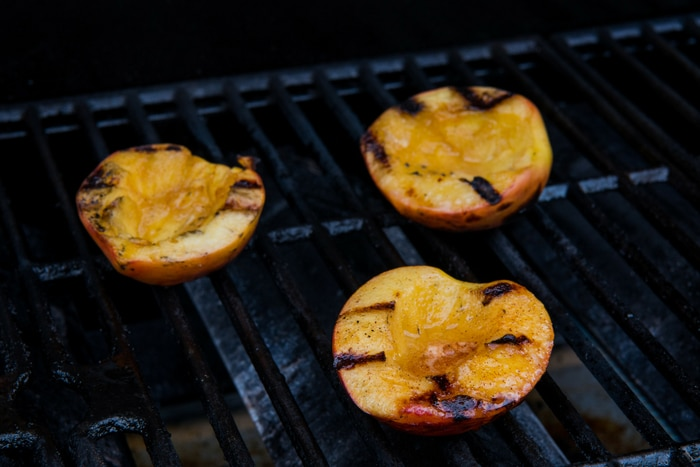 Grilling peaches on barbecue