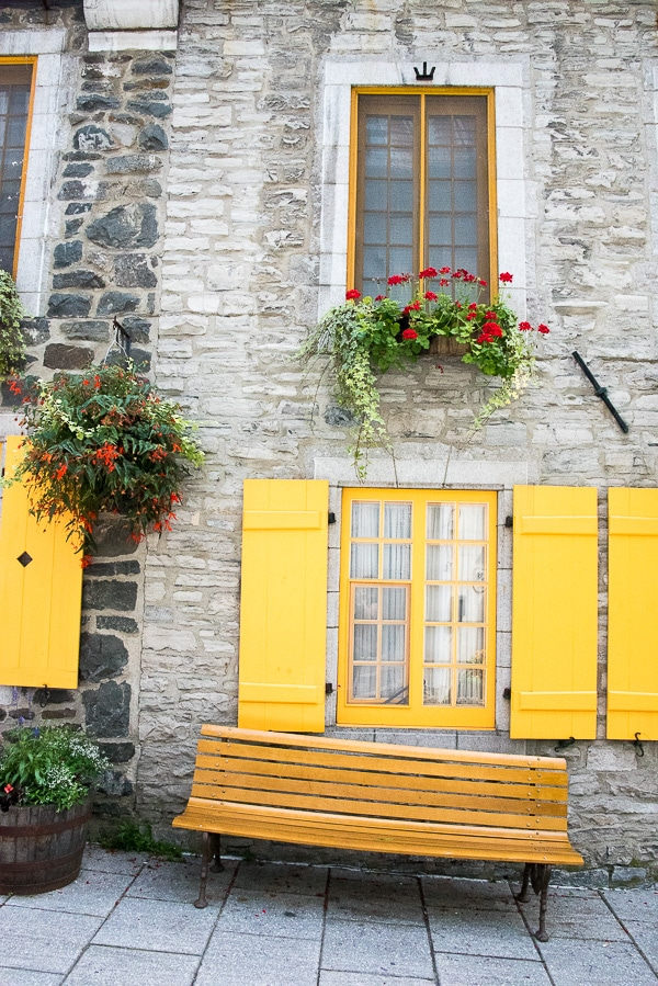 Quebec City, Lower City Stone Building with Yellow Shutters and Wooden Bench BoulderLocavore.com