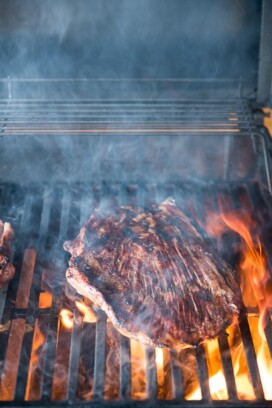 steak on grill with flames