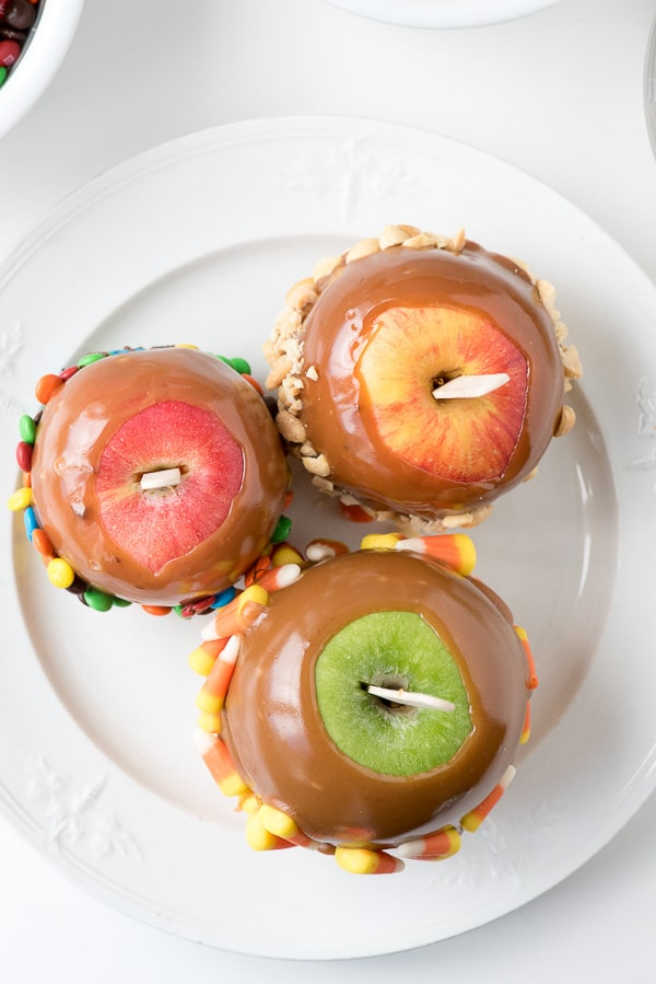 red and green apples dipped into caramel with sticks