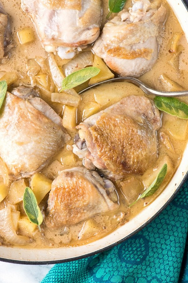 Cider-braised Chicken Thighs with Apples and Onions in French braising pan - BoulderLocavore.com