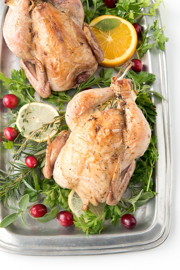Lemon Herb Roasted Cornish Game Hens served on a pewter platter with greens and lemon wedges