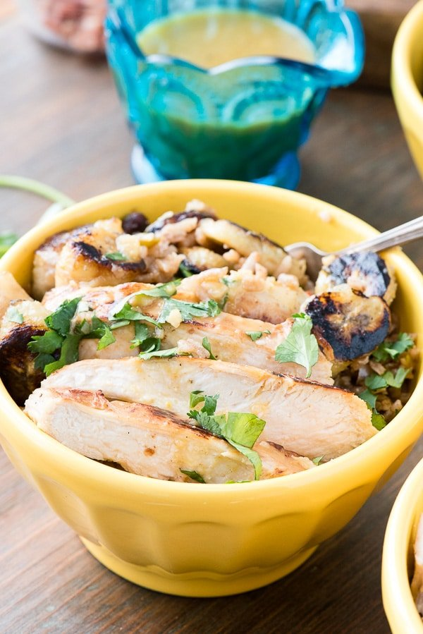 Cuban Garlic Chicken Bowls with Cuban Black Beans & Rice, Fried Plantains & Mojo Sauce served in a bright yellow bowl