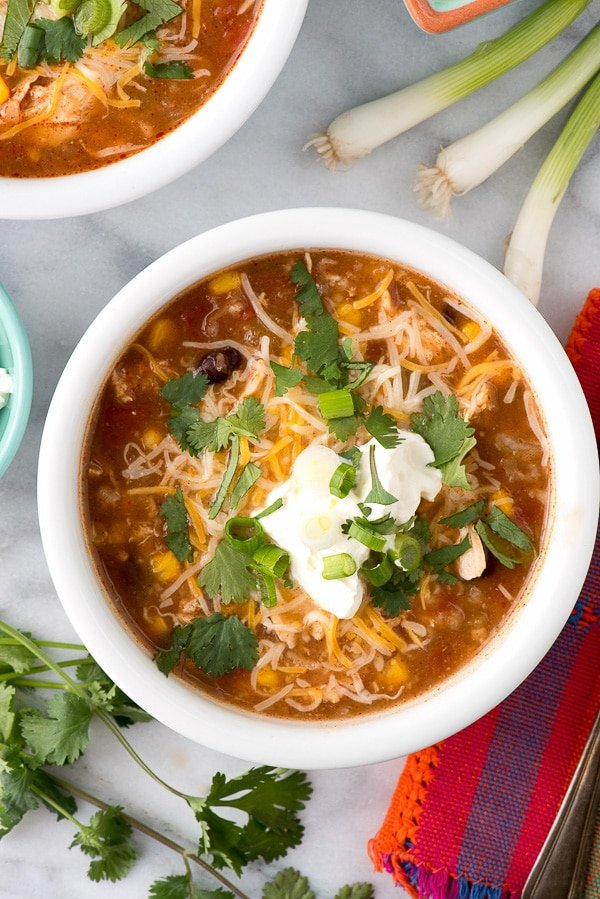 Slow cooker chicken soup made with Mexican spices is sure to become a favorite cool weather soup recipe. Spicy Slow Cooker Mexican Chicken and Rice Soup has shredded chicken, tomatoes, corn and more.
