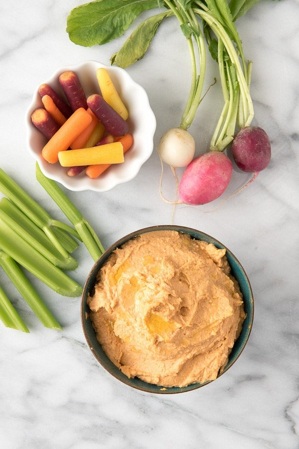 Sriracha Hummus in a bowl with a side of raw vegetables for dipping