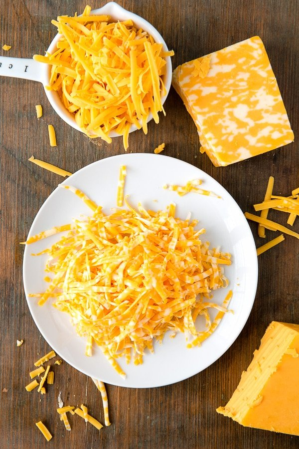 Mild Cheddar and Colby/Jack Cheese grated on a white plate
