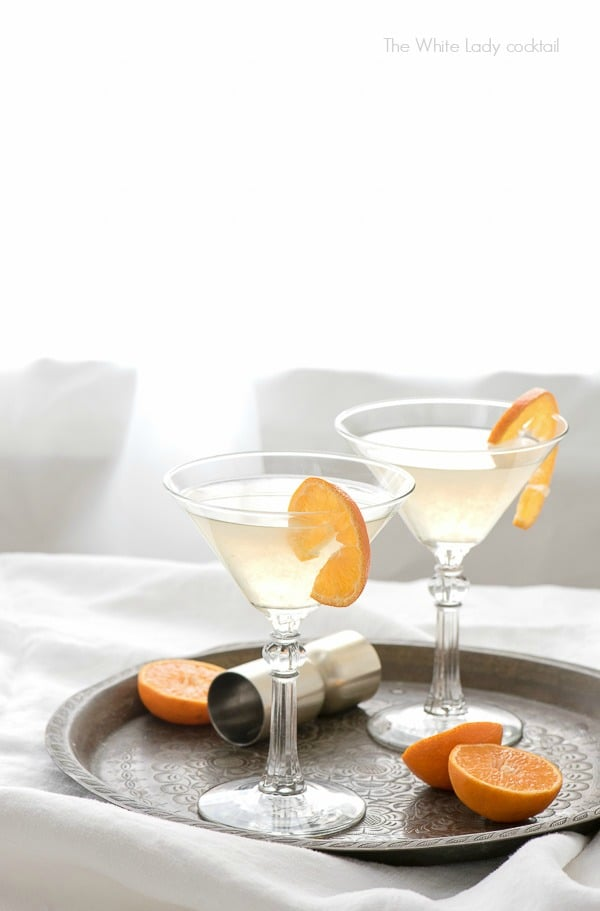 Two The White Lady Cocktails in martini glasses with orange slices on an antique bronze tray