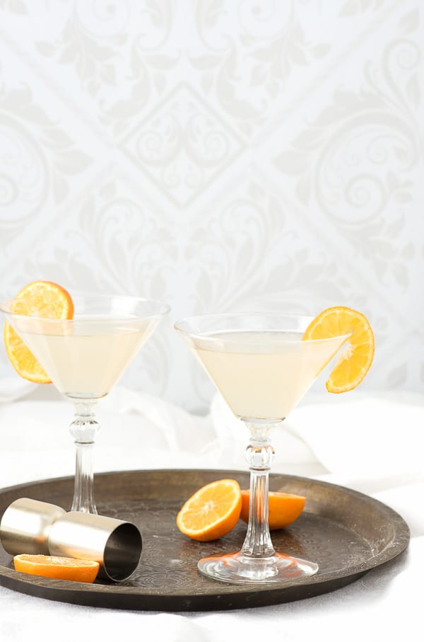 The White Lady Cocktail in cocktail glasses with orange slices and cocktail jigger on bronze tray