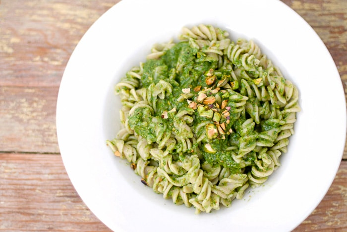 white pasta plate with Toasted Pistachio Arugula Pesto with Brown Rice Fusili Pasta