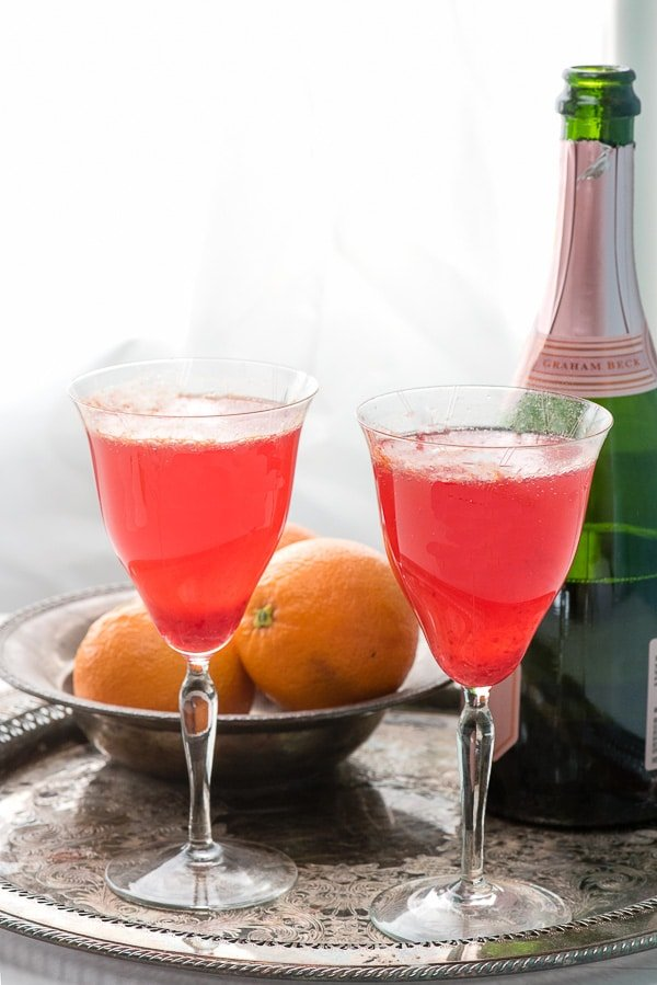 Two antique glasses of blood orange mimosas