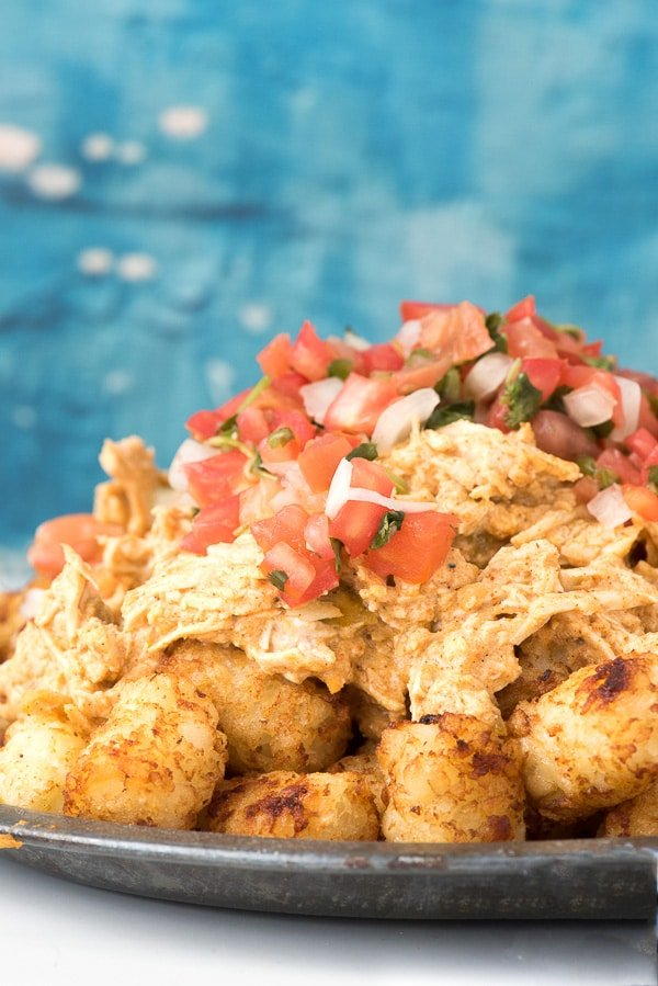 Green Chile Chicken Totchos smothered in creamy Green Chile Chicken and topped with pico de gallo