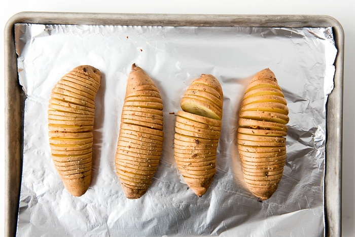 aluminum foil lined baking sheet holds 4 unbaked Hasselback style Sweet Potatoes