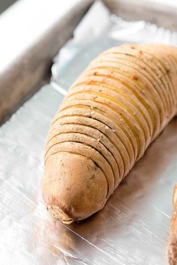 Hasselback style Sweet Potato on a baking sheet, ready for baking