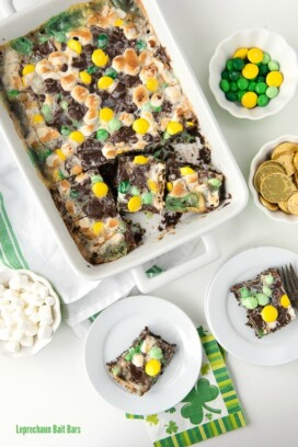 chocolate mint Leprechaun Bait Bars baked into a white baking dish, surrounded by some of the ingredients used to make them