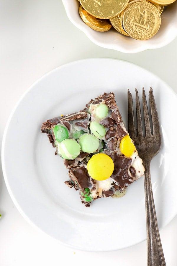 white dessert plate holding a slice of Leprechaun Bait Bar dessert and a fork.
