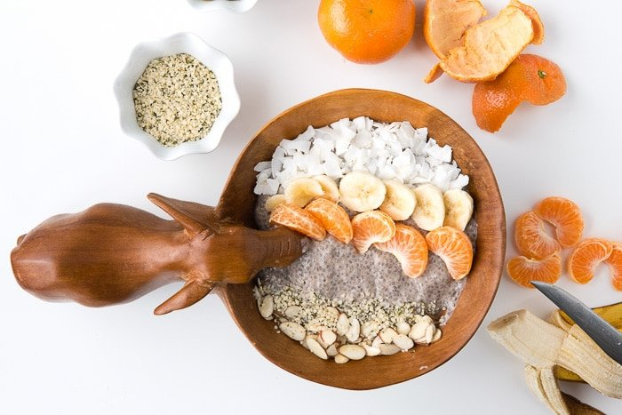 Roasted Banana Chia Pudding Breakfast Bowl surrounded by some of the fresh ingredients used to make it