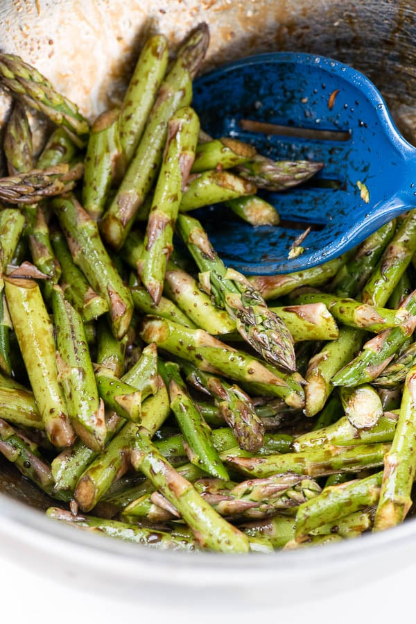 bowl of Balsamic Roasted Asparagus Spears with a royal blue serving spoon