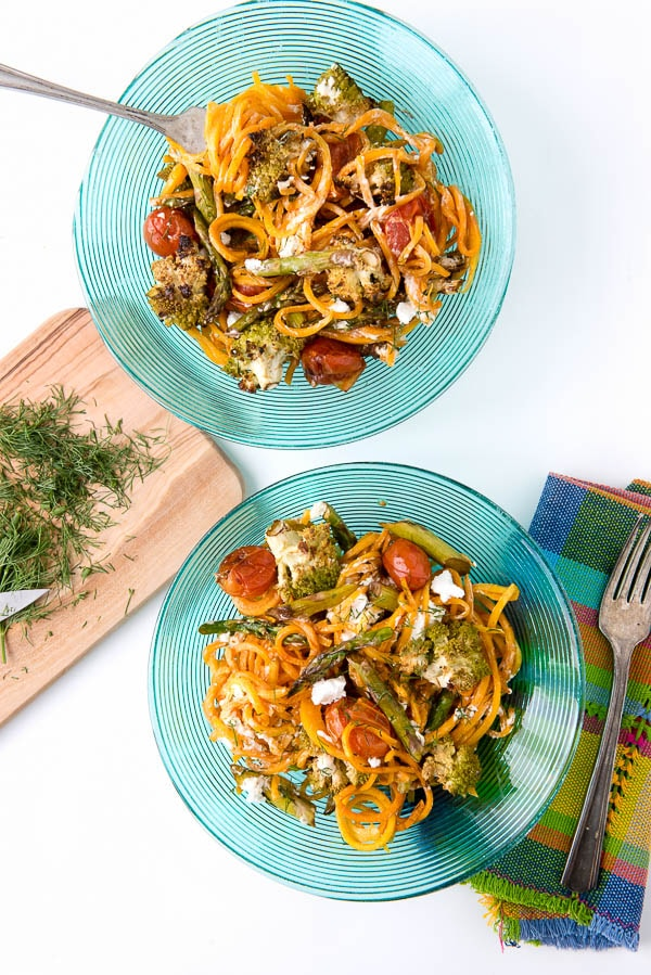 2 dinner plates with Balsamic Roasted Spring Vegetables on top of Butternut Squash Noodles