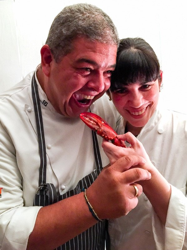 Chefs Alex and Sarah Martinez playfully cooking with crab claws