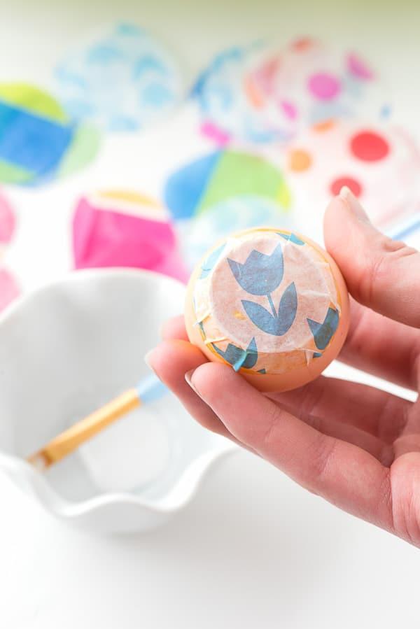 sealed homemade confetti egg with flower tissue paper on an orange egg
