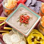 platter holding fresh vegetables and chips for dipping and a bowl of gluten free black bean green chile hummus dip