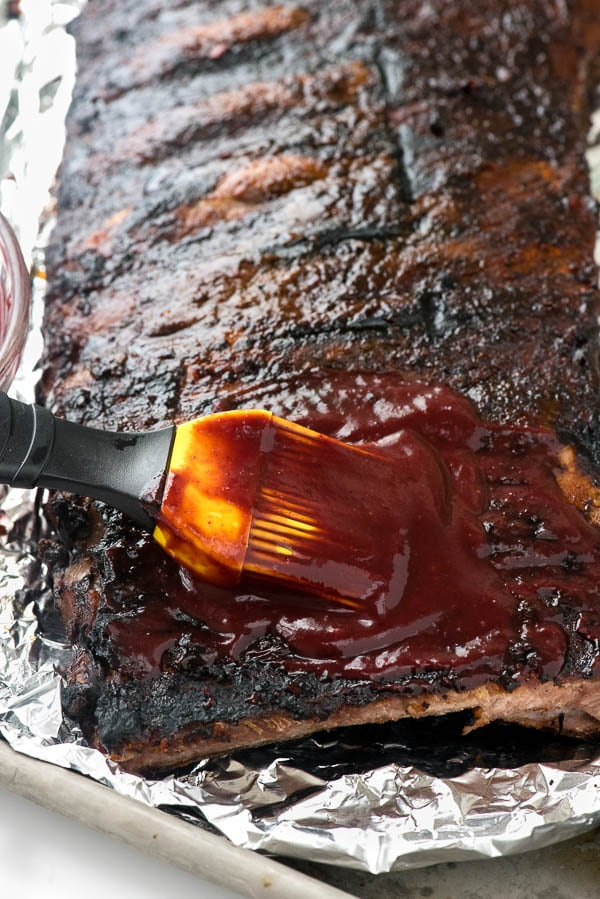 Homemade Blueberry Whiskey Barbecue Sauce being brushed onto a rack of ribs
