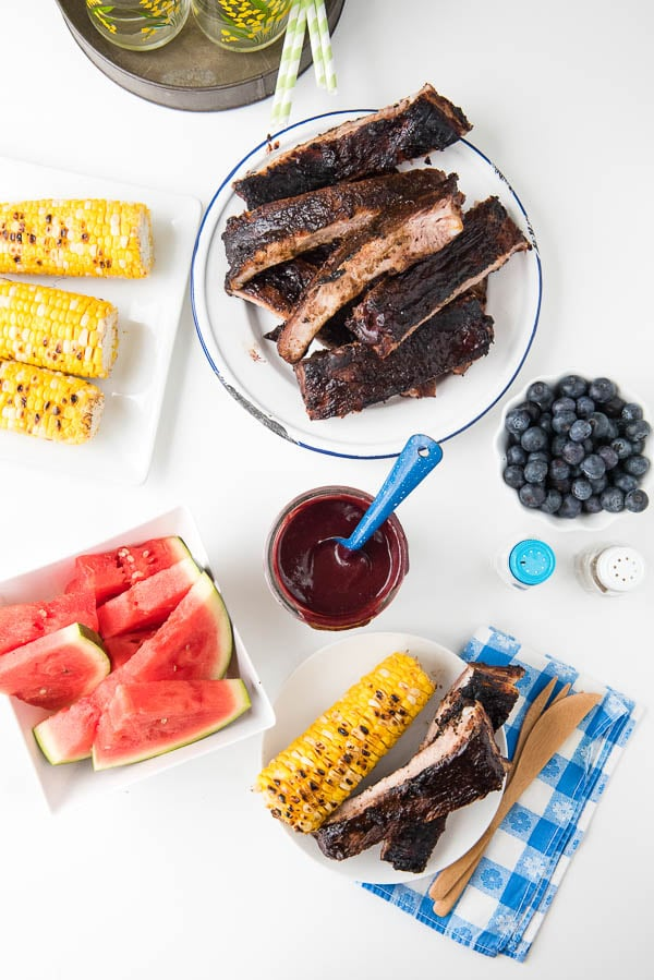 overhead image of a picnic dinner with grilled ribs, corn on the cob, watermelon, and a jar of homemade barbecue sauce