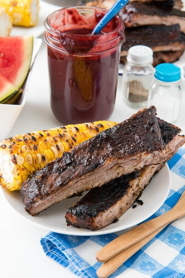 Homemade Blueberry Whiskey Barbecue Sauce in a mason jar next to a plate of grilled ribs and corn on the cob